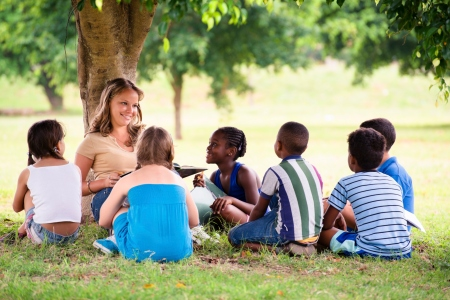 Sitting female teacher surrounded by school-aged children